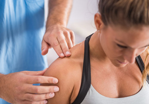 Attractive young woman receiving chiropractic treatment on her shoulder