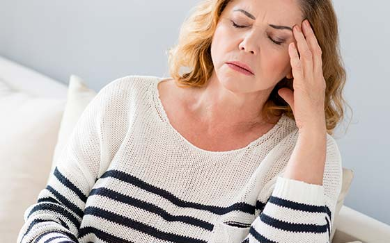 Middle aged woman suffering from an intense migraine